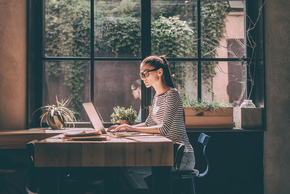 窓際の机で勉強するメガネをかけた女性