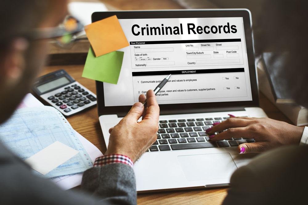 「Criminal Records」を表示したノートパソコンとそれを見る人達