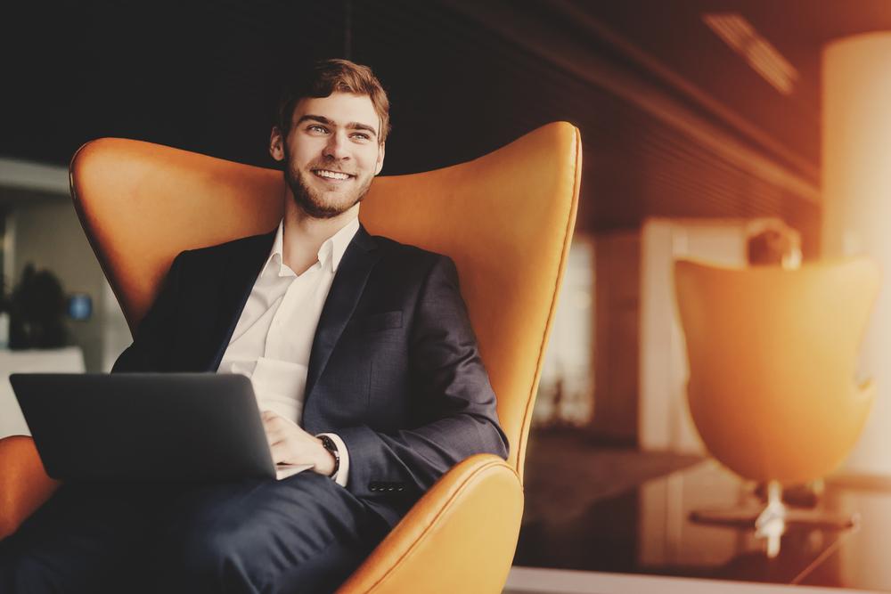 大きな椅子に腰掛けて笑顔で仕事をする男性