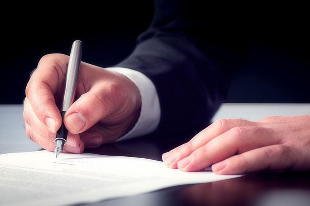 契約書を書くスーツ姿の男性