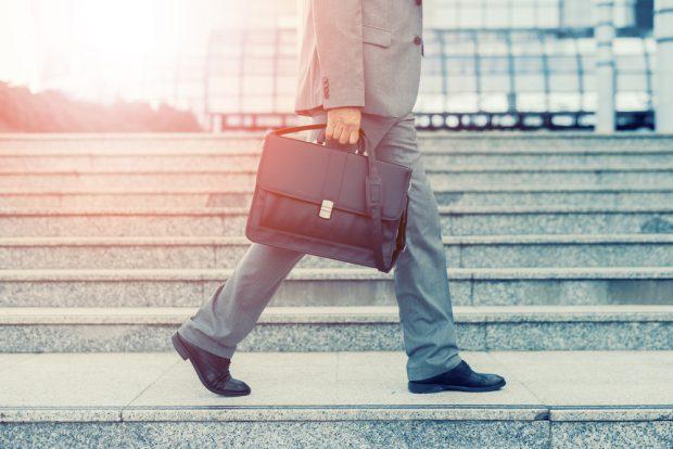 スーツを着てカバンを持ち、街を歩く男性