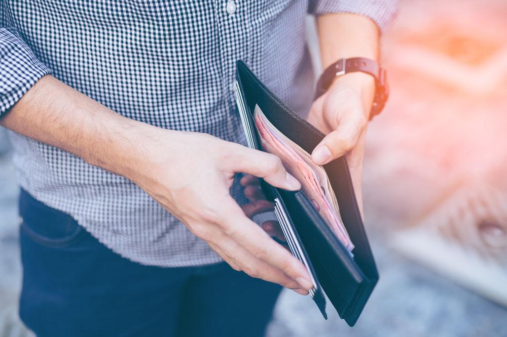 財布に中身を見せる男性