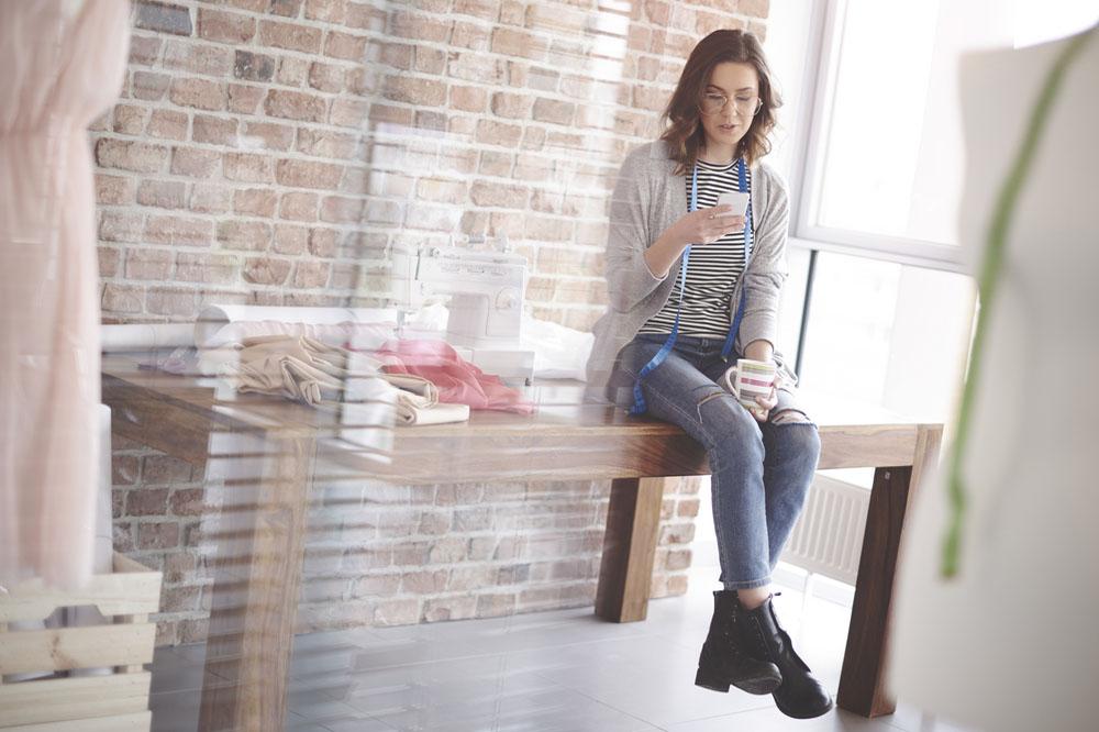 机に腰掛けてスマートフォンを見る女性