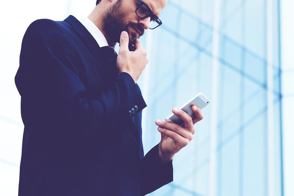 スマートフォンを見ながら顔をしかめて考える男性