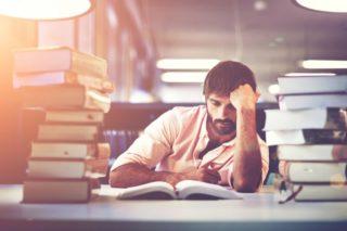 高く積み重なった本の間で考え込む男性