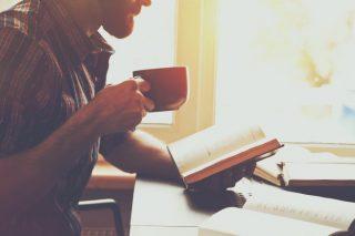 たくさんの本を読んで勉強する男性