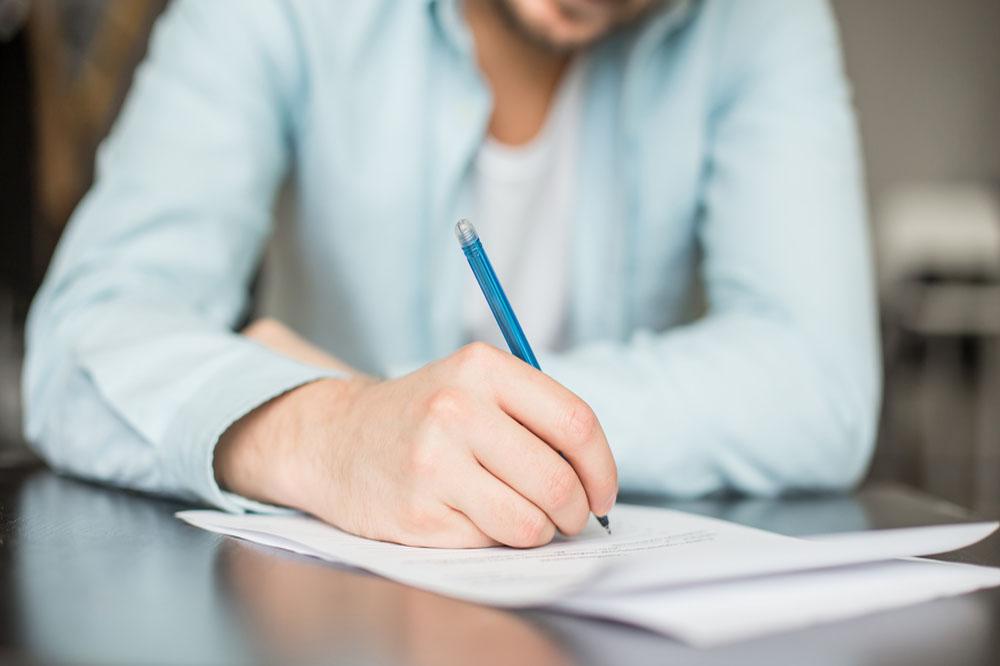 ボールペンで履歴書を書く男性