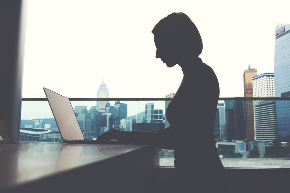 ノートパソコンを使って仕事をする女性のシルエット