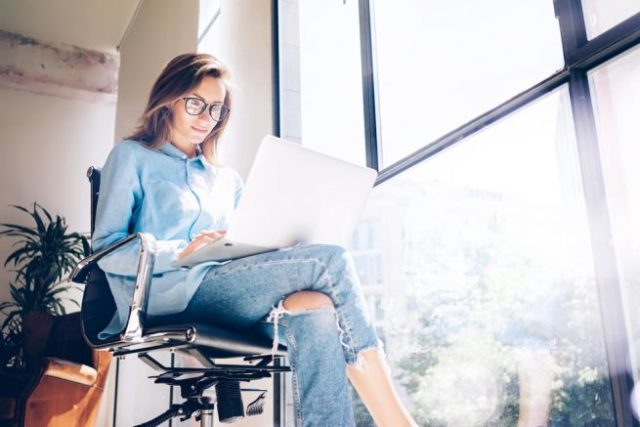 椅子に座り足を組んでノートパソコンを見つめる黒縁メガネの女性