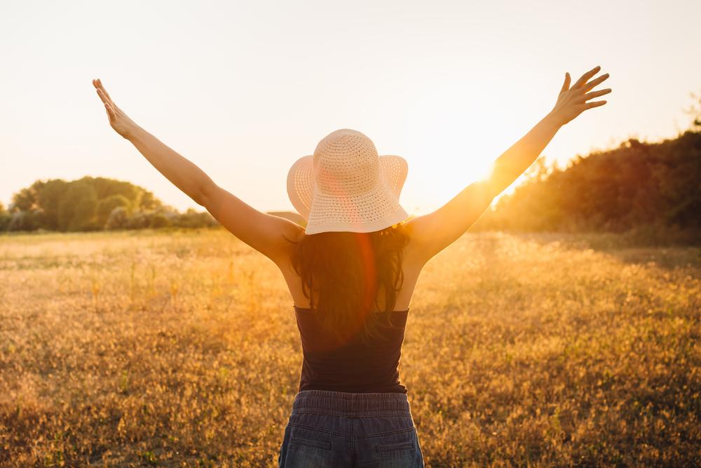草原に立ち、太陽に向かって大きく手を広げる女性