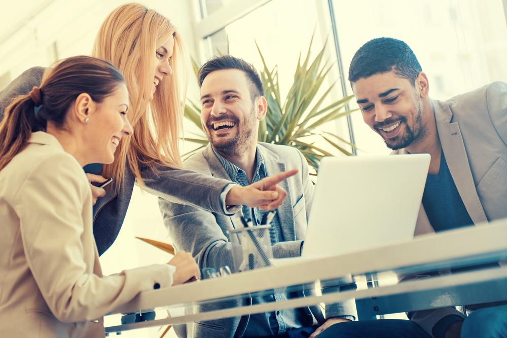 一つのノートパソコンを見ながら笑顔で仕事の打ち合わせをする人々