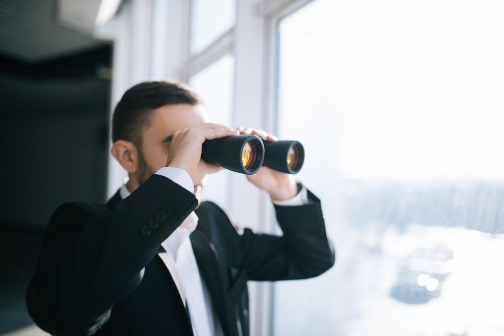 望遠鏡で遠くを眺める黒いジャケットを羽織った男性