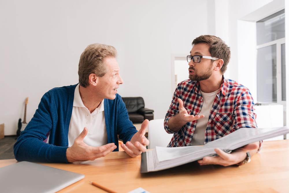資料を見ながら話し合う男性