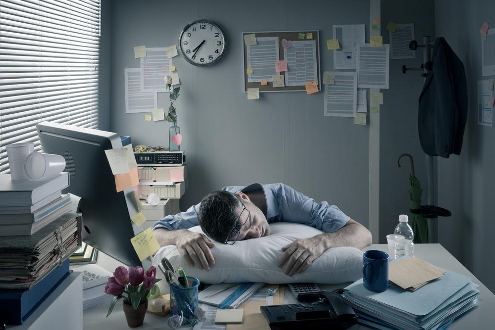 オーバーワークの為に職場のデスクで仮眠をとる男性