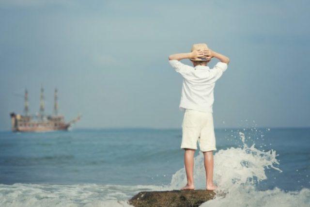波しぶきがたつ岩場で、海に浮かぶ船を眺める少年