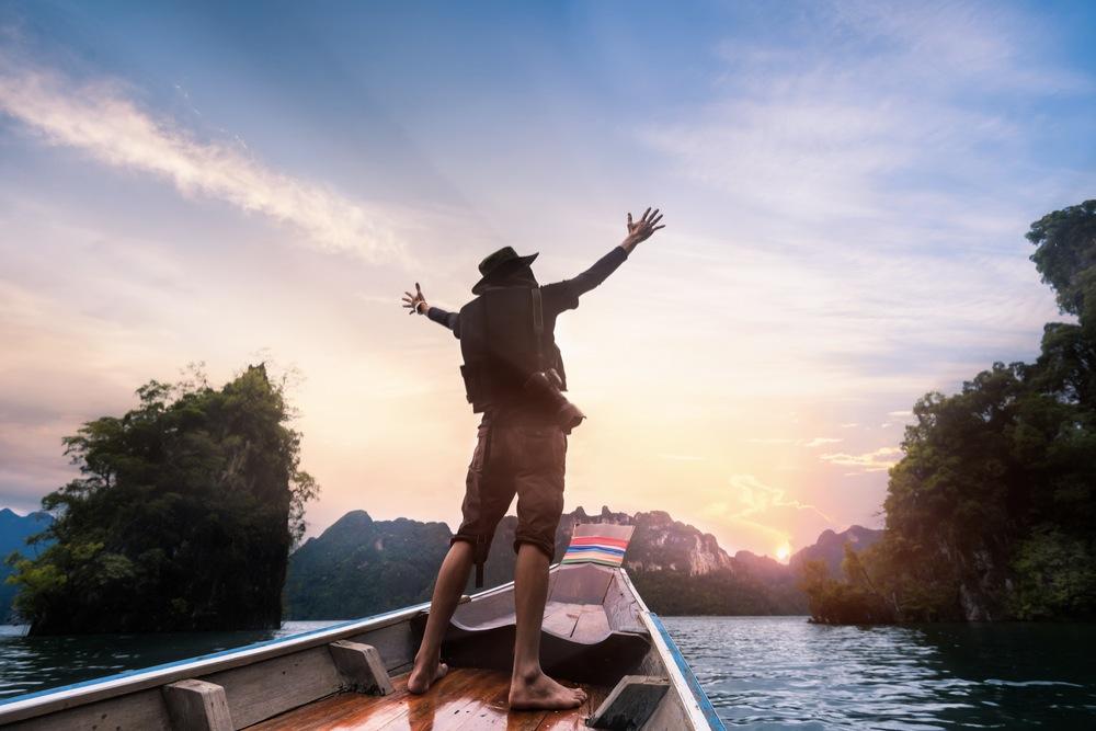 小舟の先端に立って、朝日位向かって大きく手を広げる人