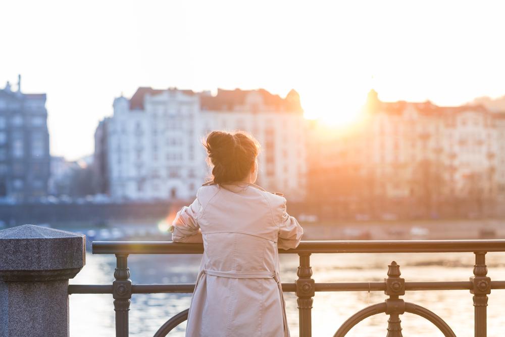 川辺に立って夕日を見つめる女性