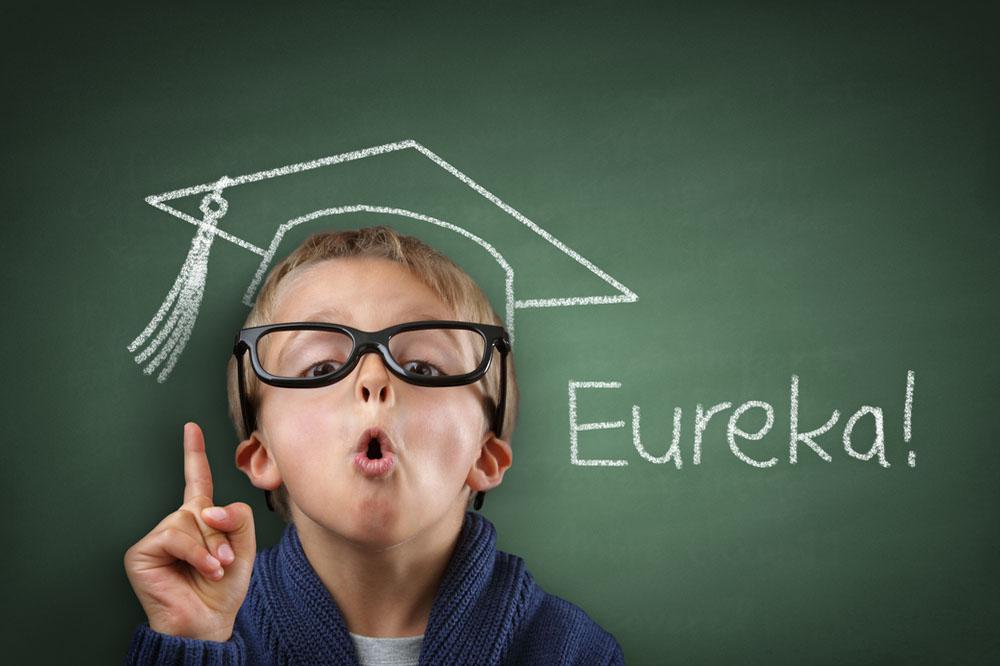 「Eureka!」と書かれた黒板と、黒縁メガネをかけた子供
