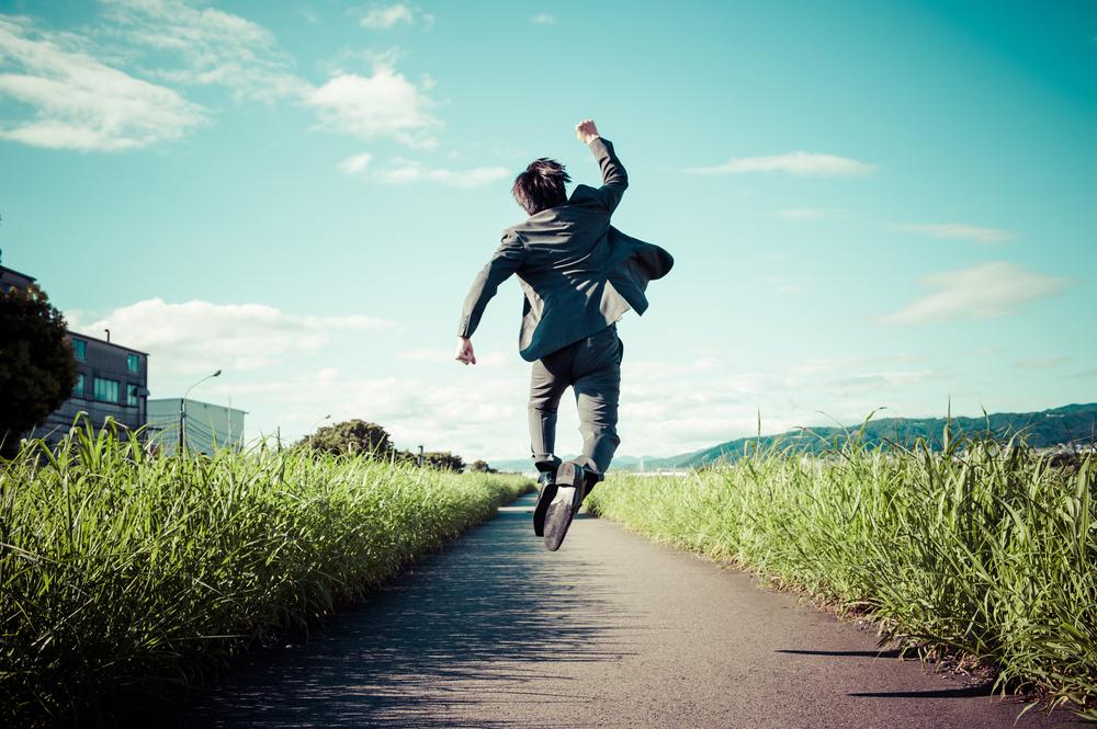 青空に向かってジャンプしながらガッツポーズする男性