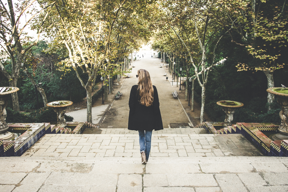公園を1人歩く長い金髪の女性