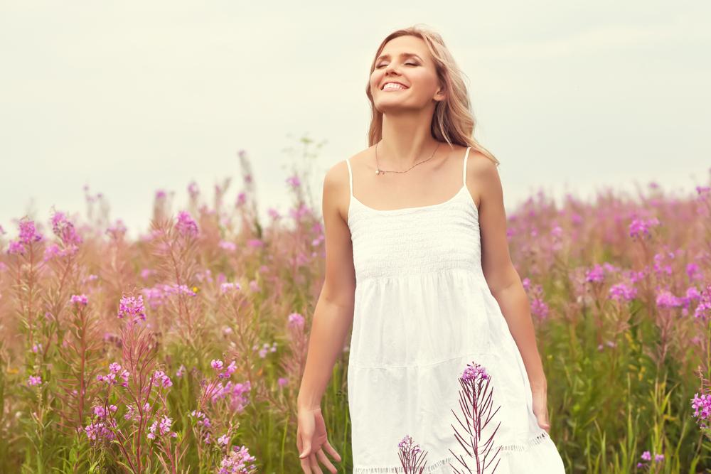 花が咲く草原で晴れやかな顔で立つワンピース姿の女性