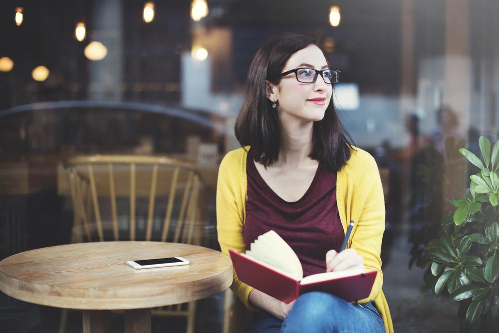 オープンカフェで考え事をする黒縁メガネの女性