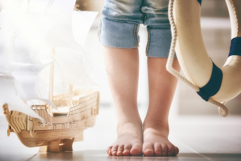 船の模型と浮き輪を持つ子供