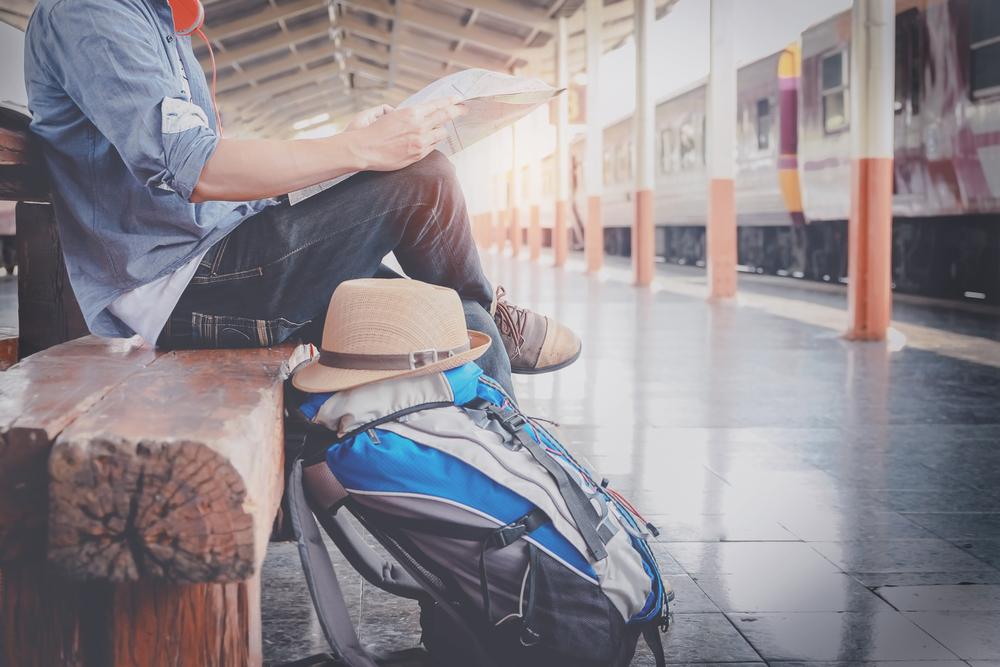 駅で電車を待つ、大きなバックパックを持つ男性