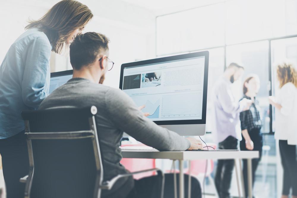 パソコンを見ながら仕事の会話をする男女