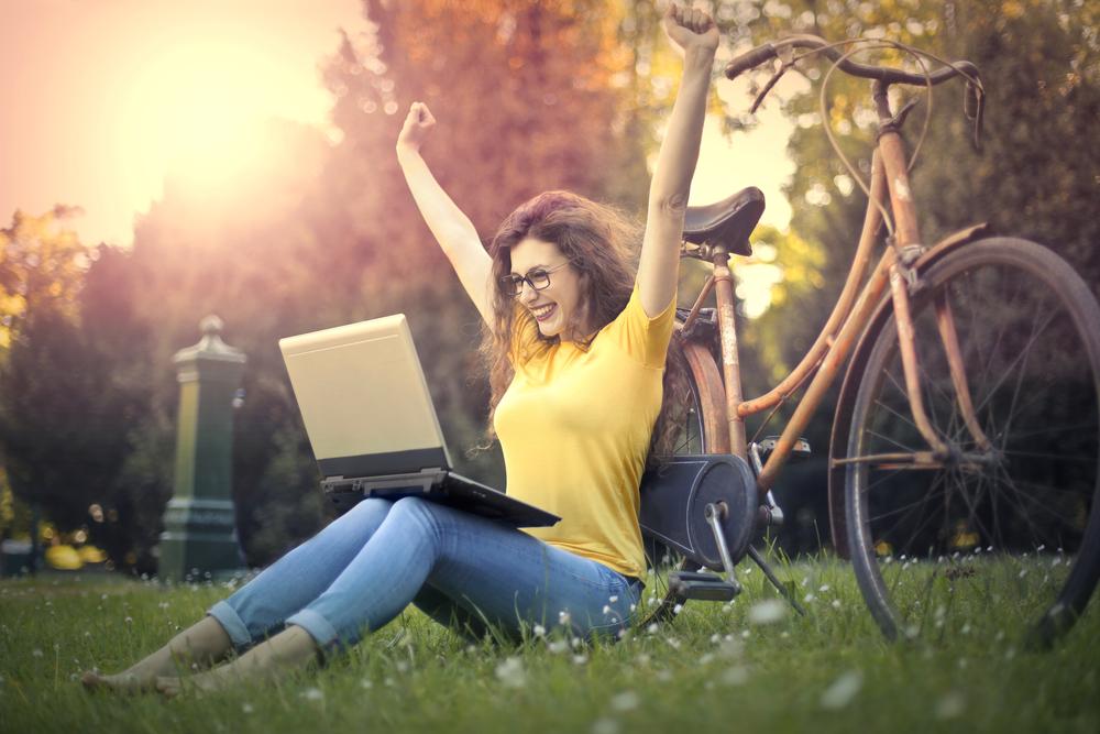 ノートパソコンの画面を見て喜ぶ女性