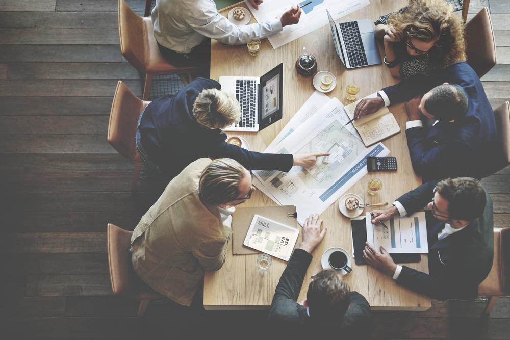 大きな机に座って活発に会議する人々