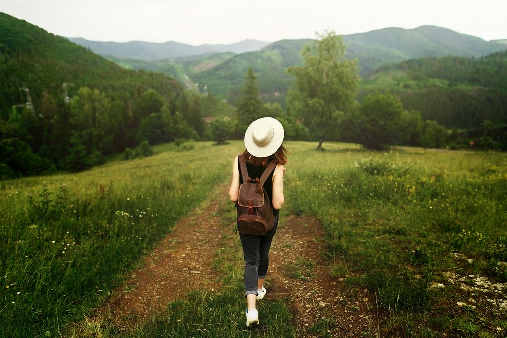 田舎の一品道を歩く白い帽子をかぶった女性