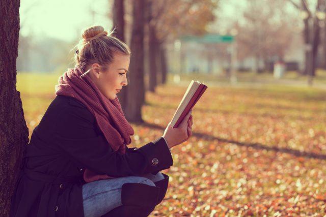 秋の公園でしゃがみながら本を読む女性