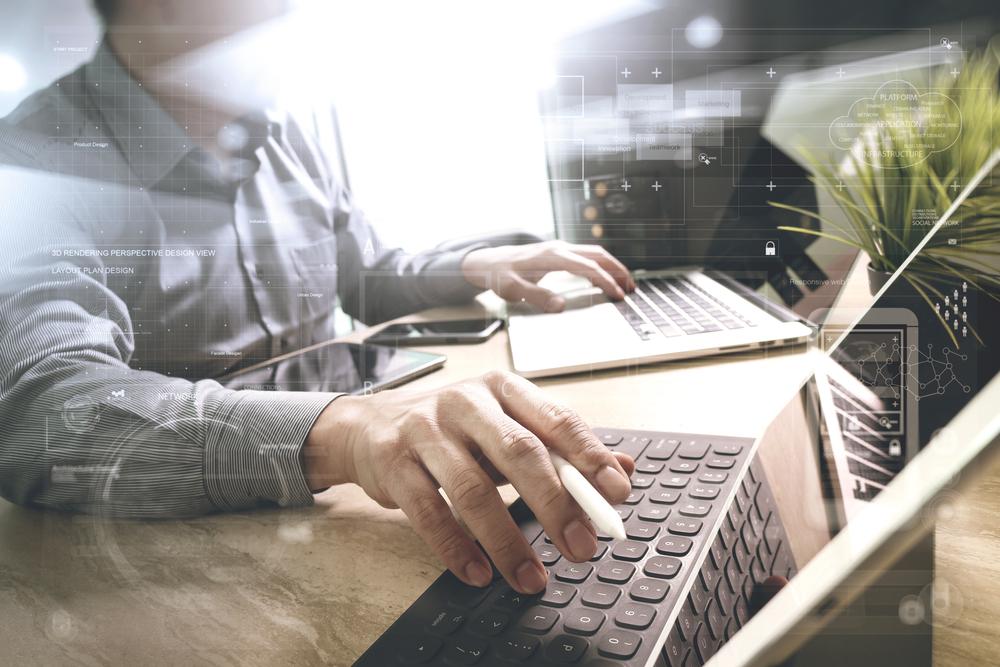 二つのパソコンを使って効率よく仕事をする男性