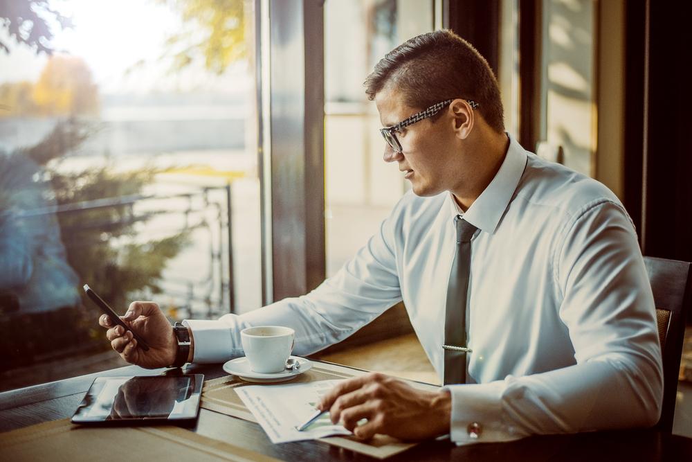 カフェで仕事をしながらスマートフォンを見るビジネスマン