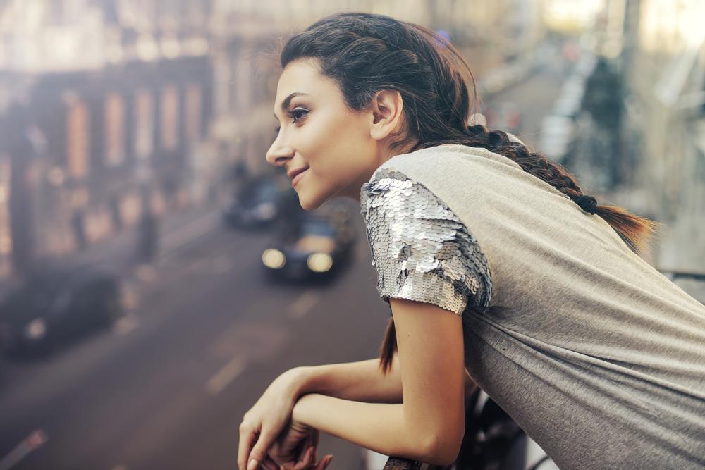 都会のマンションの窓から街を見下ろす女性