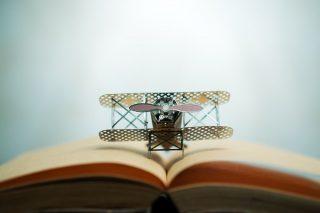 開いた本とおもちゃの飛行機