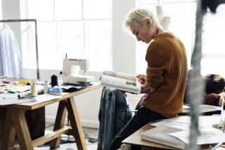 机に腰掛けて雑誌を眺める女性
