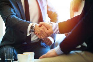 握手を交わすスーツ姿の2人の男性
