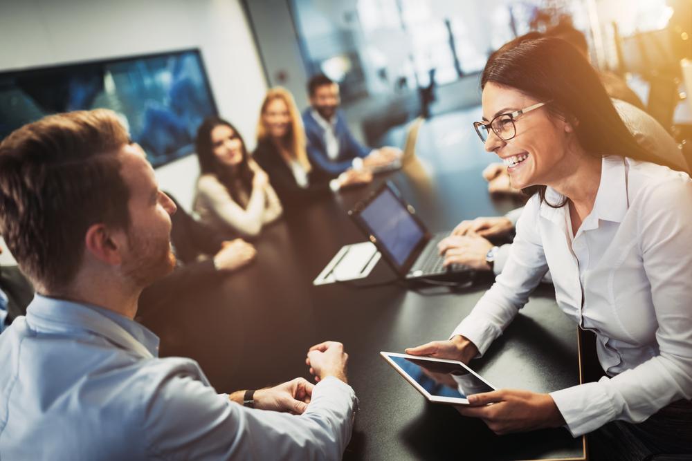 会議中に笑顔で話をする男女