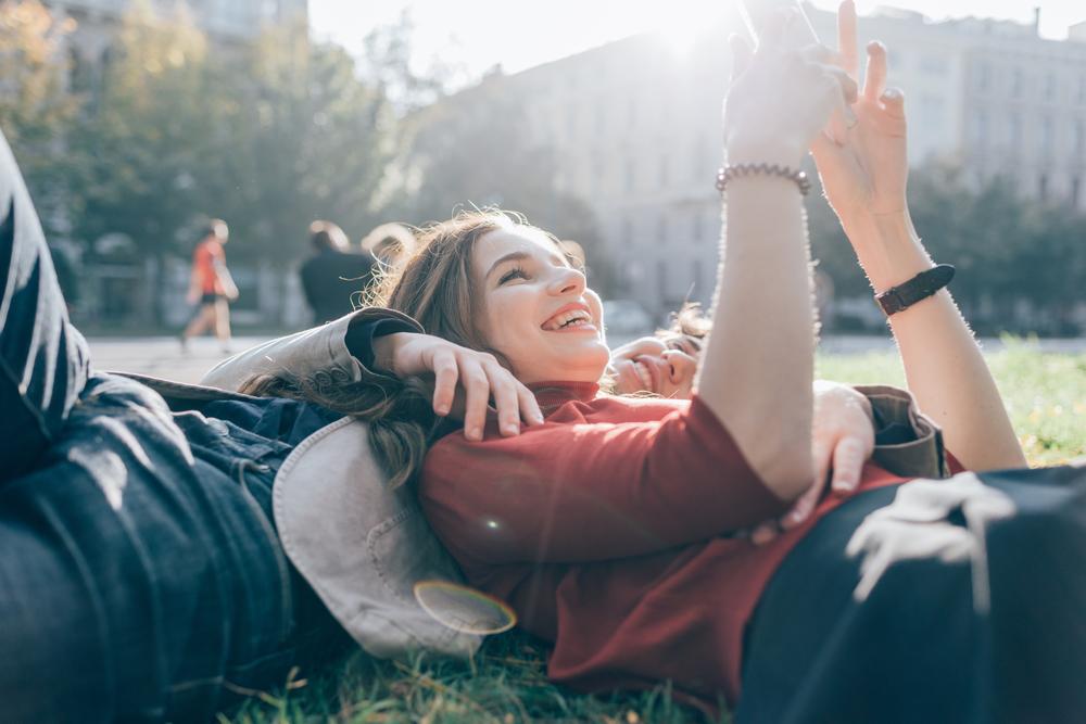 芝生に寝転んでスマートフォンを見るカップル