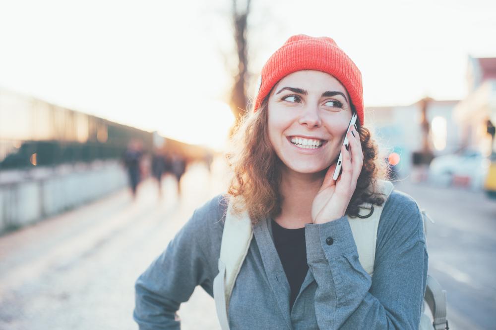 スマートフォンで通話しながら街を歩く女性