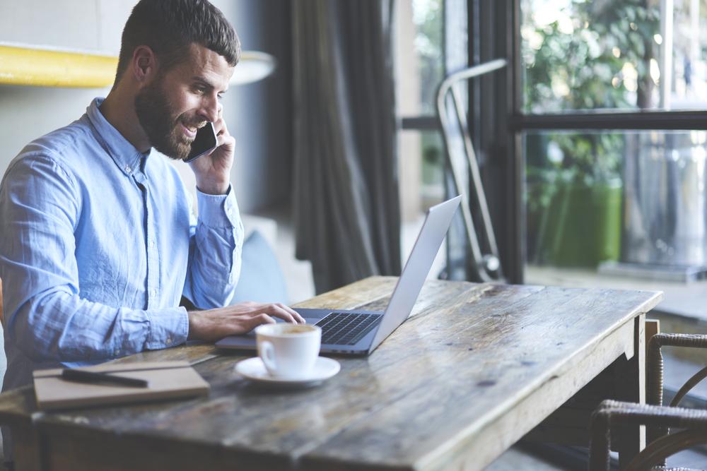 ノートパソコンを開きながら笑顔で電話する男性