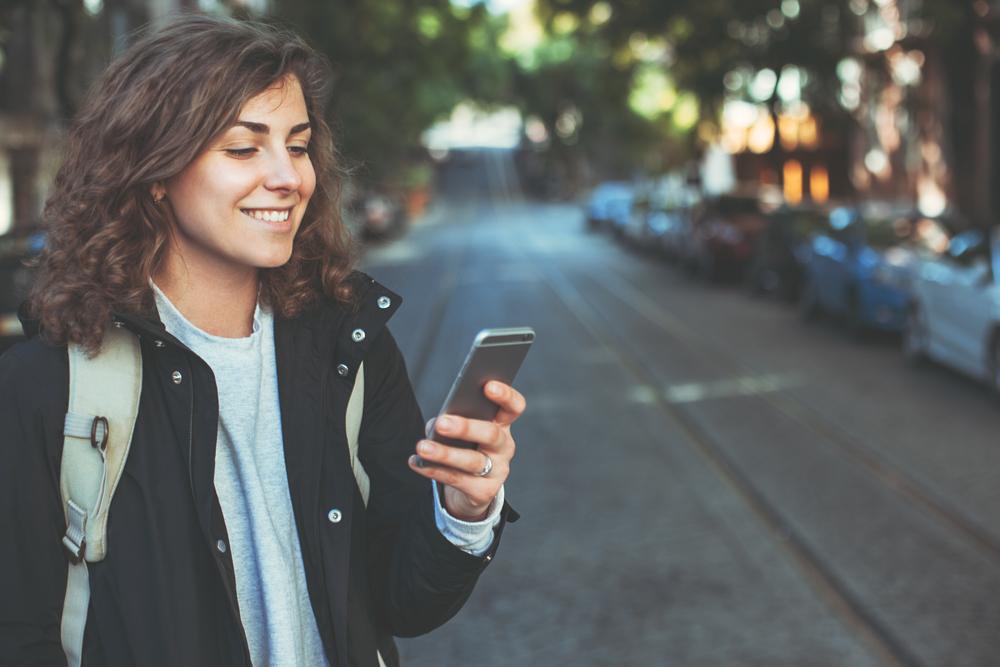 街中で立ち止まり、笑顔でスマートフォンを見る女性