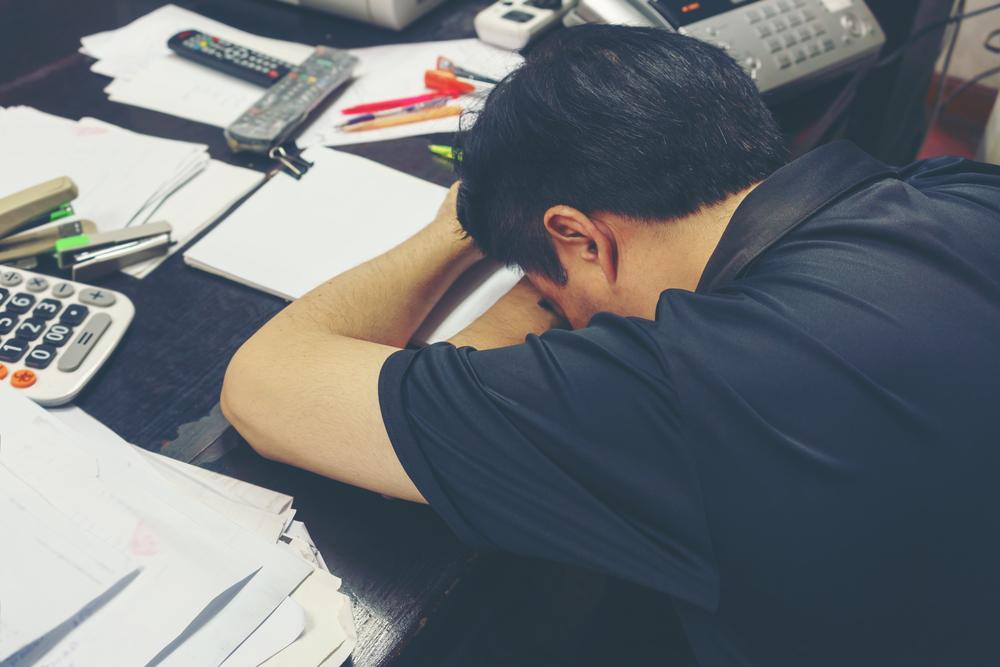 文房具などが散乱した部屋で机に突っ伏して寝る男性