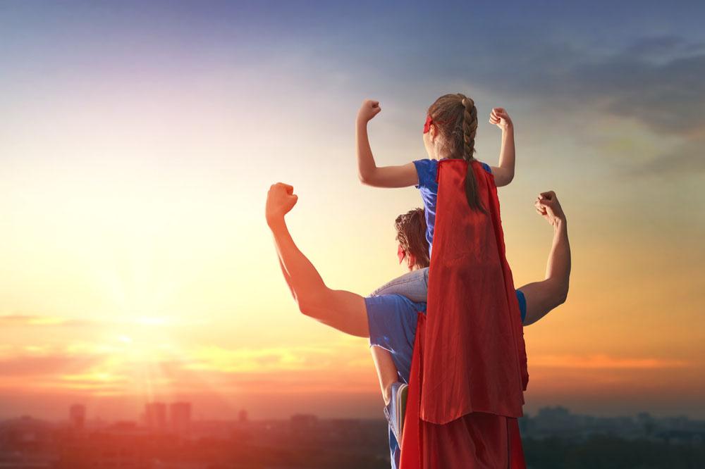 スーパーマンの格好をしてガッツポーズする親子