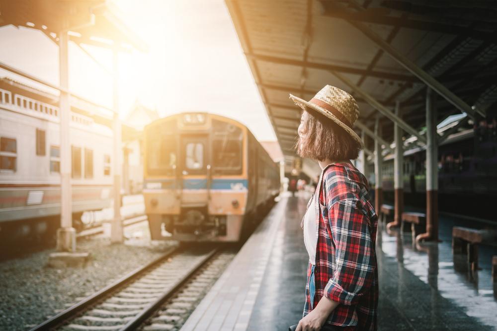 駅で電車を待つ麦わら帽子をかぶった女性