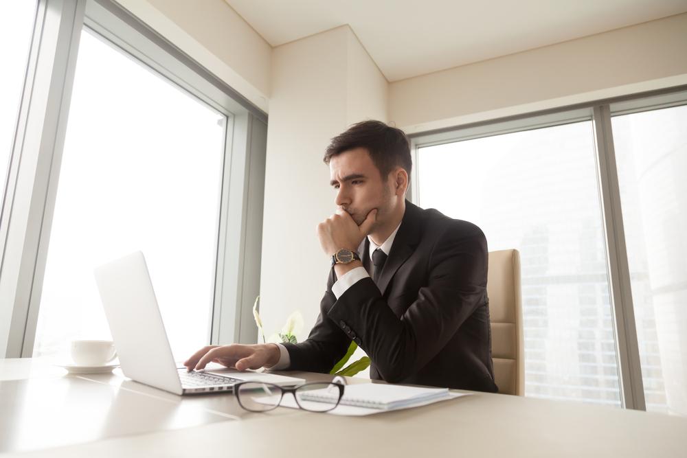 ノートパソコンを見ながら悩むビジネスマン