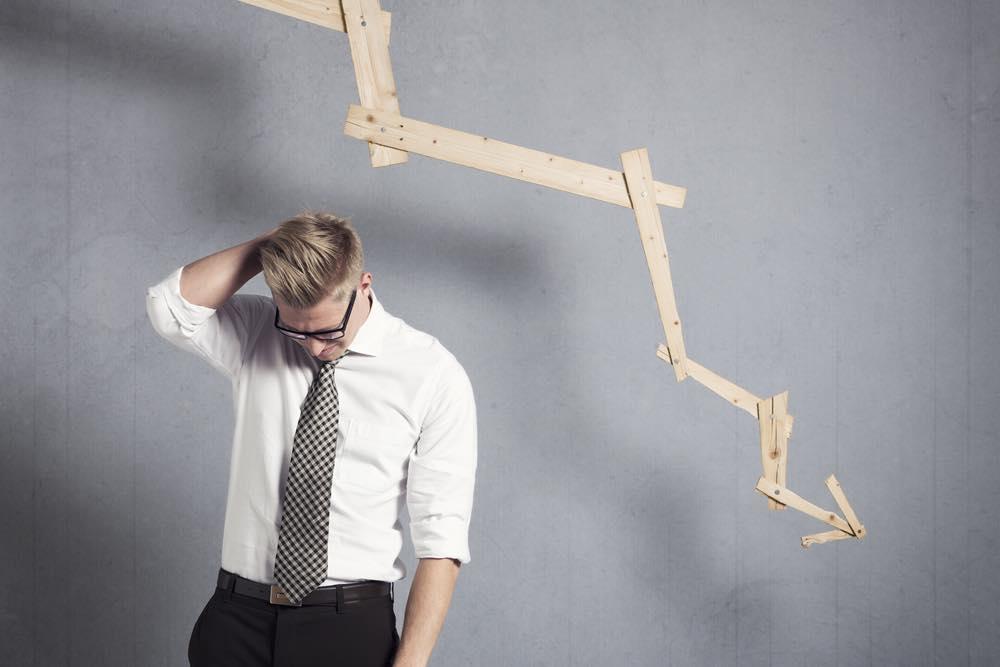 右肩下がりのグラフと頭を掻いて悩む男性