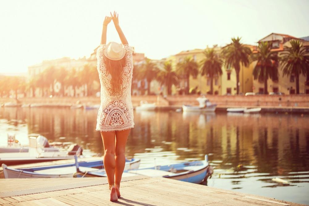 リゾート地の水辺で伸びをする女性